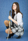Girl with sword sit on a blue background — Stock Photo