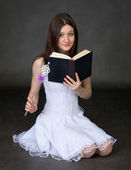 Girl with the book and a magic wand — Stock Photo