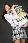 Schoolgirl bearing pile of books — Stock Photo