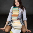 Schoolgirl and the big pile of books on a black — Stock Photo #2292368