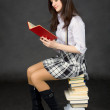 Girl reads the book, sitting on pile of books — Stock Photo #2292379