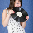 Girl biting a phonograph record on a blue — Stock Photo