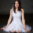 Girl in white dress sits on a black — Stock Photo