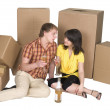 Girl and the guy drink champagne near boxes — Stock Photo