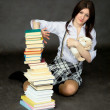 Schoolgirl with pile of books and toy — Stock Photo