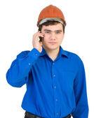 Człowiek w kasku mówi przez telefon — Zdjęcie stockowe