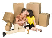 Girl and guy drink champagne near boxes — Stock Photo