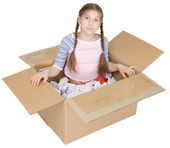 Little girl sits in a cardboard box — Stock Photo