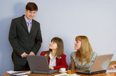Girls at a desktop and their chief — Stock Photo