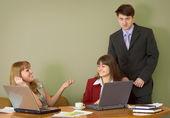 Meninas em um ambiente de trabalho e o chefe deles — Fotografia Stock