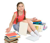 Schoolgirl among a heap of books — Stock Photo