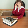 Stock Photo: Young girl in office armchair with typewriter
