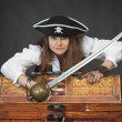 Woman pirate with a sabre and treasures - Stock Photo