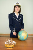 Girl in a uniform of captain with globe — Stock Photo