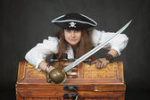 Woman pirate with a sabre and treasures — Stock Photo