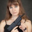 serious beauty armed with submachine gun on a bl — Stock Photo