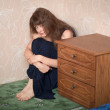Sad girl in a dress sits in a corner - Stockfoto