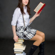 Beautiful young woman reads on a pile of books o — Stock Photo