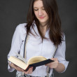 Beautiful young woman reads big book on black ba — Stock Photo