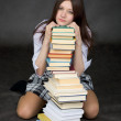 Girl sits on a floor embracing of books — Stock Photo