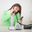 Girl at office talks by several phones simultane — Stock Photo