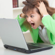 Stock Photo: Young girl shouts looking in laptop screen