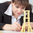 图库照片: Young girl in black concentrated builds tower of