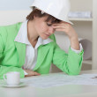 Tired wom- engineer in helmet sits at table i — Stock Photo #2314555