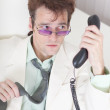 Stock Photo: Businessmemotionally speaks on phone at offic