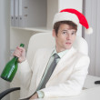 Young man in Christmas cap sits with bottle at t — Stock Photo