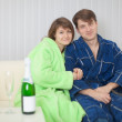 Young pair on a sofa with sparkling wine — Stock Photo