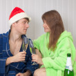 Young pair drinks champagne sitting on sofa in d — Stock Photo