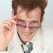 Cheerful tousled guy looks over eyeglasses — Stock Photo