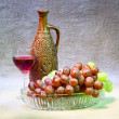 Still-life with clay bottle, grapes and glass on — Stock Photo