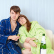 Young pair at home on sofa with sparkling wine — Stock Photo