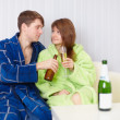 Young pair at home on divan with beer and wine — Stock Photo