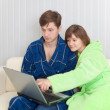 Guy and woman sit on sofa with laptop — Stock Photo