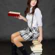 Schoolgirl sits on big pile of books — Stock Photo #2317602