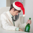 Drunk man in a Christmas cap with bottle sits at — Stock Photo