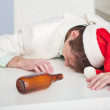 Stock Photo: Drunk person in Christmas cap lies on white ta