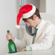Drunken man in Christmas cap with bottle in a ha — Stock Photo