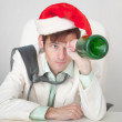 Amusing guy in Christmas cap with bottle in a ha — Stock Photo