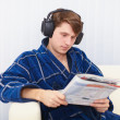 Man in big ear-phones on sofa reads newspaper — Stockfoto