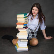 Stock Photo: Schoolgirl with amazement looks at books