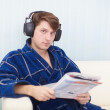 Man in big ear-phones on sofa reads newspaper — Stock Photo #2319554