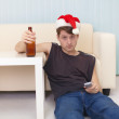 Young man in christmas hat sits on a floor with — Stock Photo