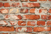 Brick wall of red color with cracks and stains — Stock Photo