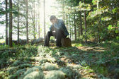 Sad young man sits in wood on stone — Stock Photo