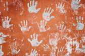 Concrete red wall with prints of hands — Stock Photo