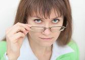 Strikt unga kvinnan ser på oss över glasögon — Stockfoto